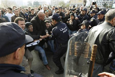 Algerian policemen try to take away a banner from anti-government protesters during a demonstration in Algiers February 12, 2011. REUTERS/Zohra Bensemra