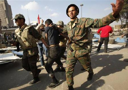 Egyptian soldiers drag away a suspect from opposition supporters at the frontline near Tahrir Square in Cairo February 12, 2011. REUTERS/Suhaib Salem