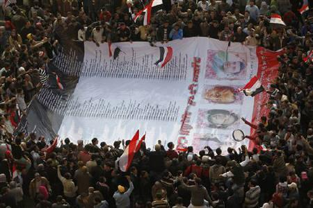 Protesters carry a big banner which has names and some pictures of protesters who were killed during the uprising in Cairo in Tahrir Square February 11, 2011. REUTERS/Asmaa Waguih