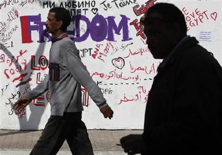People walk past slogans near Tahrir Square in Cairo February 13, 2011. REUTERS/Asmaa Waguih