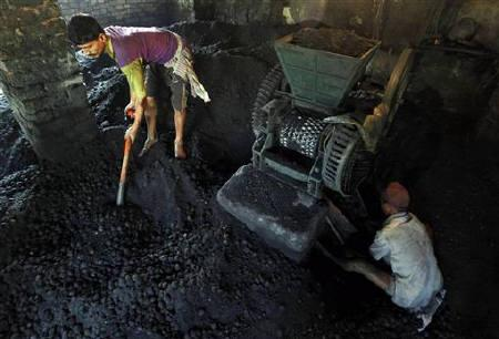 Labourers work inside a coal ball factory in Kolkata November 4, 2010. REUTERS/Rupak De Chowdhuri/Files