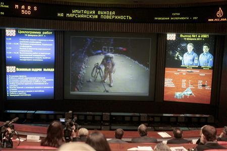 Technicians watch a feed from the Mars 500 project at mission control in the town of Korolyov on the outskirts of Moscow February 14, 2011. A crew of six who began a simulated real time 520 day mission to Mars, transmitted pictures of a simulated Mars landing on Monday after 233 days in a locked steel capsule. REUTERS/Alexander Natruskin