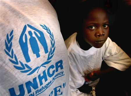 A boy returning from exile in Sierra Leone travels on the back of a U.N. lorry to a transit centre in his native Liberia on World Refugee Day, June 20, 2006. REUTERS/STR New