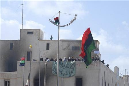 Demonstrators wave flags and hold banners on the roof of burnt building in this undated picture made available on Facebook February 20, 2011. The image was purportedly taken recently in Benghazi. REUTERS/Handout