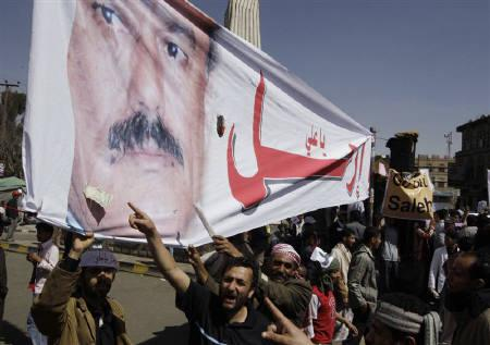 Anti-government protesters shout slogans as they point at a poster of Yemen's President Ali Abdullah Saleh during a protest outside Sanaa University February 21, 2011. REUTERS/AMMAR AWAD
