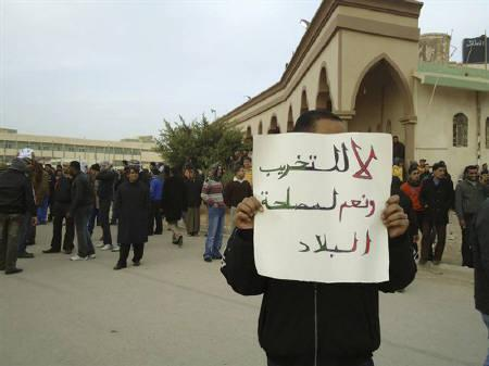 A man holds up a placard during a demonstration in the seaport city of Tobruk February 20, 2011.  REUTERS/Stringer