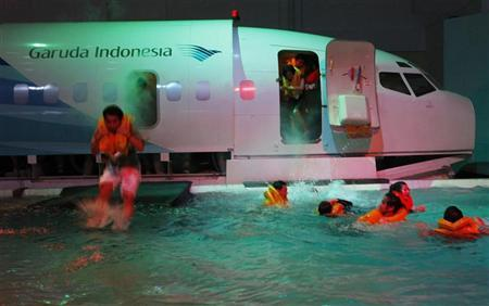 Flight attendant trainees jump out of a mock up of an aircraft during an emergency evacuation drill at the Garuda Indonesia Training Centre in Jakarta January 25, 2011. REUTERS/Beawiharta (INDONESIA - Tags: BUSINESS TRANSPORT EMPLOYMENT)