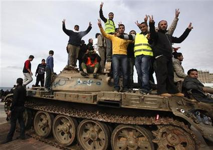 Anti-government protesters make victory signs as they stand on an army tank near a square where people are protesting in Benghazi city, Libya, February 23, 2011. REUTERS/Asmaa Waguih
