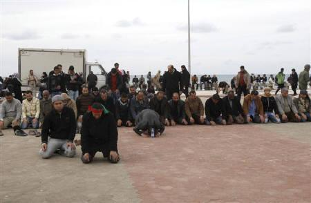 Anti-government protesters pray by the seaside near a square where people gather for protests in Benghazi city, Libya, February 23, 2011. REUTERS/Asmaa Waguih