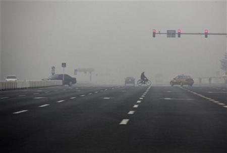 Thick pollution can be seen as a man rides his bicycle across the main road running through Beijing's Tiananmen Square February 21, 2011. REUTERS/David Gray