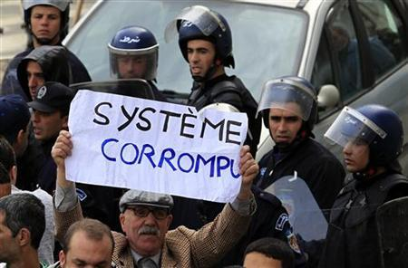 An anti-government protesters holds a sign on which reads ''Corrupted system'' during a demonstration in Algiers February 19, 2011. REUTERS/Zohra Bensemra