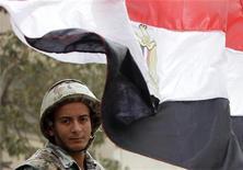 <p>جندي يقف بجانب العلم المصري في ميدان التحرير بالقاهرة يوم الجمعة. تصوير: محمد عبد الغني - رويترز</p>