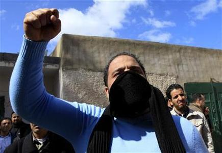 A Libyan mourner chants anti-Gaddafi slogans during the funeral of Anwar Elgadi, 44, who was killed the previous day by security forces according to his brother Mohammed, in the Tajoora neighborhood of Tripoli February 26, 2011. REUTERS/Ahmed Jadallah