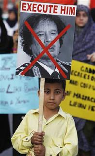 A Shiite Muslim supporter of Majlis e Wahdat e Islami holds up a poster depicting Libyan leader Muammar Gaddafi as he marches with others in support of the people of Libya, Tunisia, Bahrain, Egypt and Yemen during a rally in Karachi February 27, 2011. REUTERS/Akhtar Soomro