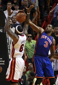 Miami Heat's LeBron James (L) is blocked as he goes up to shoot against New York Knicks' Shawne Williams during fourth quarter NBA basketball action in Miami, Florida February 27, 2011. REUTERS/Hans Deryk