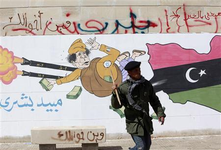 An anti-government rebel stands in front of a mural depicting Libyan leader Muammar Gaddafi in Benghazi February 28, 2011. REUTERS/Asmaa Waguih