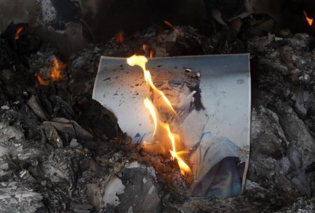 People burn pictures of Libyan leader Muammar Gaddafi inside the main prison of Gaddafi's forces in Benghazi, February 28, 2011. REUTERS/Suhaib Salem