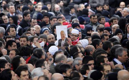 A man holds a portrait of Turkey's former Prime Minister Necmettin Erbakan during his funeral in Istanbul March 1, 2011. REUTERS/Osman Orsal