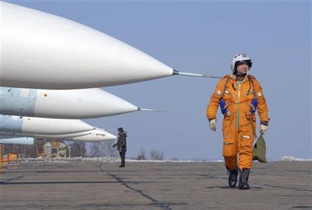 A pilot walks past SU-27SM fighter jets at a military airbase in Russia's far eastern city of Vladivostok, February 14, 2008. REUTERS/Yuri Maltsev