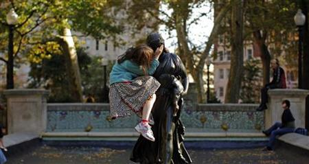A girl sits in the arms of a statue in Rittenhouse Square on a warm fall day in Philadelphia, October 17, 2010. REUTERS/Brian Snyder