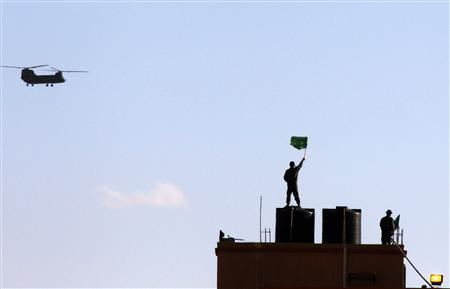 A Libyan army soldier signals at a Chinook helicopter from a rooftop, at a border crossing station in western Libya March 1, 2011. REUTERS/Yannis Behrakis