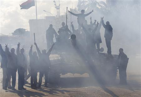 Protesters opposed to leader Muammar Gaddafi chant slogans, obscured by the engine smoke of a tank of Libyan army defectors, in the city of Zawiyah, 50 km (30 miles) west of the capital Tripoli, March 1, 2011. REUTERS/Ahmed Jadallah