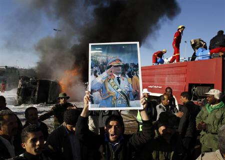 A poster of Libya's leader Muammar Gaddafi, one of several which were distributed among a crowd gathered to view a burning fuel truck, is held in front of the media in Tripoli March 2, 2011. REUTERS/Chris Helgren