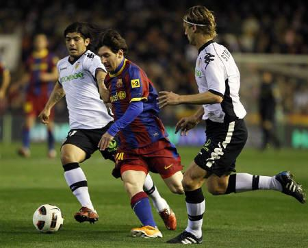 Barcelona's Lionel Messi (C) and Valencia's Ever Banega (L) and Marius Stankevicius fight for the ball during their Spanish first division soccer match at the Mestalla Stadium in Valencia, March 2, 2011.  REUTERS/Heino Kalis