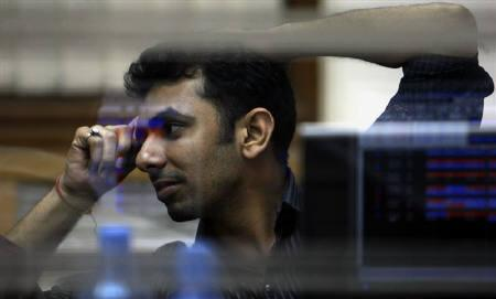 File photo of a broker while trading at a stock brokerage firm in Mumbai November 11, 2008. Diversified stock funds lagged the Sensex in February, as exposure to mid- and small-cap shares and sectors like capital goods hurt net asset values. REUTERS/Arko Datta/Files