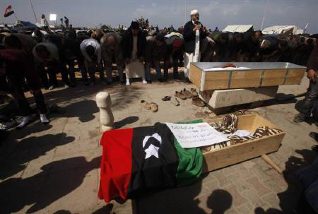 Mourners pray next to coffins containing the bodies of rebels killed in clashes with forces loyal to Libyan leader Muammar Gaddafi in Brega, during their funeral in Benghazi March 3, 2011. REUTERS/Suhaib Salem
