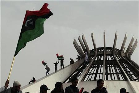Protesters wave a Kingdom of Libya flag atop a burnt state security building during protests in Benghazi, March 2, 2011. REUTERS/Suhaib Salem
