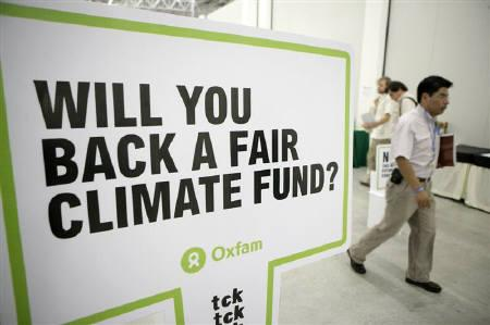 A man walks past a sign by Oxfam at the Cancunmesse convention center where climate talks are taking place in Cancun December 1, 2010. REUTERS/Gerardo Garcia/Files