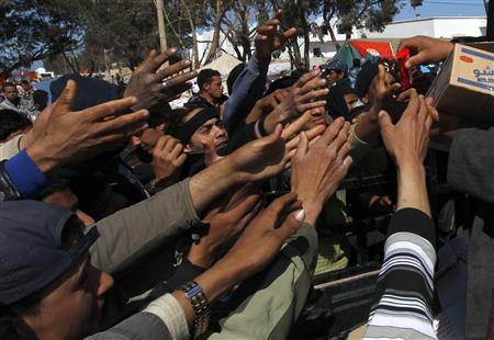Egyptian evacuees scramble to receive food after crossing into Tunisia, fleeing violence in Libya at the border crossing of Ras Jdir March 3, 2011. REUTERS/Yannis Behrakis