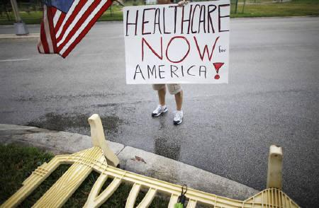 A supporter of the health care reform holds a sign outside a health care town hall meeting with U.S. congressman Kendrick Meeks (R-FL) in Miami, Florida September 3, 2009. REUTERS/Carlos Barria/Files