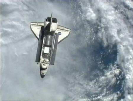 The Space Shuttle Discovery is pictured with the earth in the background as it approaches the International Space Station for docking in this still image taken from NASA TV, February 26, 2011.    REUTERS/NASA TV
