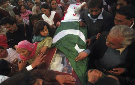 People gather near the casket of Pakistan's Minister for Minorities Shahbaz Bhatti, wrapped in national and party flags, after a funeral ceremony inside a church in Islamabad March 4, 2011. REUTERS/Faisal Mahmood