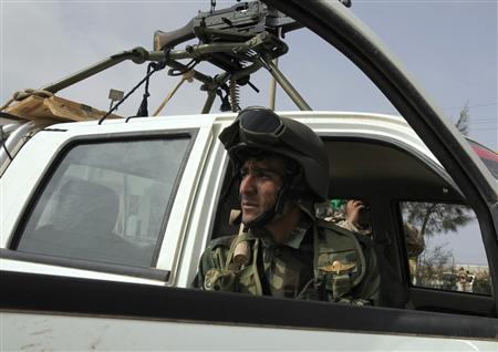 An anti-Gaddafi rebel looks out from a car in Brega March 5, 2011. REUTERS/Asmaa Waguih