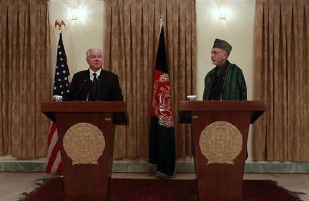 Afghanistan's President Hamid Karzai (R) looks on as U.S. Defense Secretary Robert Gates speaks during a news conference in Kabul March 7, 2011. REUTERS/Omar Sobhani