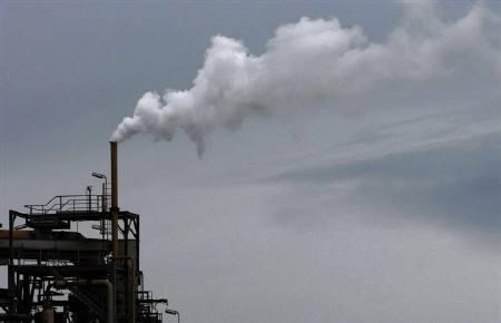 Steam and emissions are seen coming out of a funnel at an oil refinery in Melbourne July 2, 2009. REUTERS/Mick Tsikas/Files