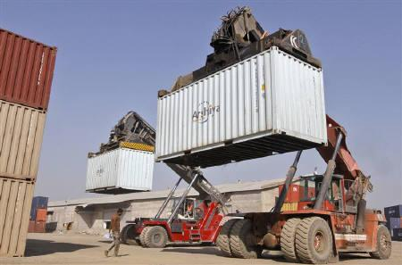Workers prepare to stack containers using cranes at Thar Dry Port in Sanand in the western Indian state of Gujarat March 1, 2011. IREUTERS/Amit Dave/Files