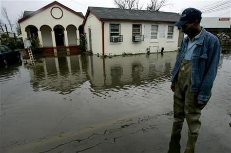 Larry Campbell of New Orleans wades in flood waters in front of his house after heavy rains caused street flooding in New Orleans, Louisiana, December 21, 2006. REUTERS/Sean Gardner