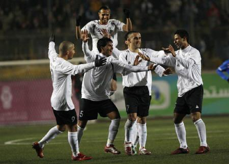 A group of Palestine's soccer players celebrate after scoring their first goal against Thailand's national team during an Olympic games qualifying match between the national soccer teams at a stadium in the West Bank town of A-Ram near Jerusalem March 9, 2011. REUTERS/Mohamad Torokman