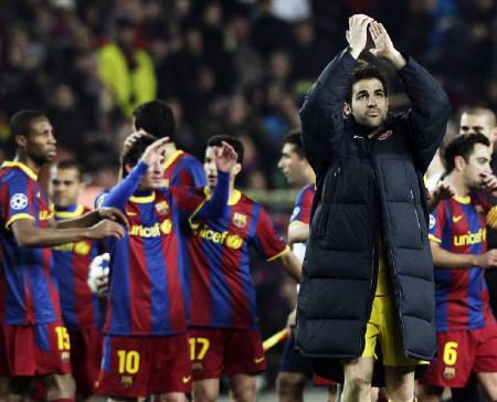 Arsenal's Cesc Fabregas (front) reacts at the end of their Champions League soccer match against Barcelona at Nou Camp stadium in Barcelona March 8, 2011. REUTERS/Albert Gea