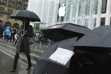 A customer occupying the first spot in line outside an Apple store holds an umbrella with a sign offering to sell the spot, as customers wait to purchase the iPad 2 in New York March 10, 2011. REUTERS/Lucas Jackson