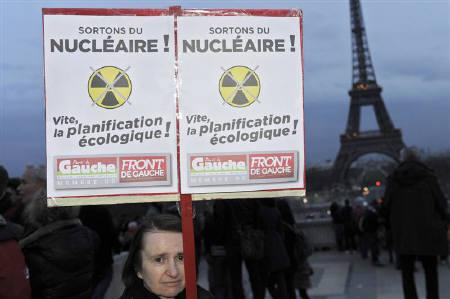 Members of the French anti-nuclear group 'Sortir du Nucleaire' particiipate in a protest demonstration near the Eiffel Tower in Paris March 13, 2011 in reaction to the nuclear power plant that was damaged after an earthquake in Japan. Signs read, 'Quick Ecological Planification.'  REUTERS/Gonzalo Fuentes