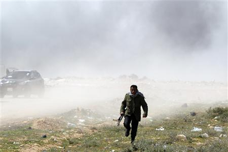 A rebel fighter runs for cover during an air strike at a rebel fighters checkpoint in Al Ugaila area along a road between the towns of Brega and Ras Lanuf, March 12, 2011. REUTERS/Goran Tomasevic