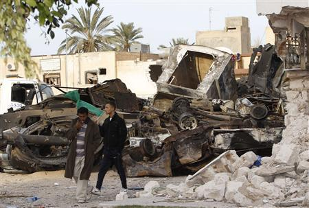 Men pass destroyed vehicles near a damaged mosque at Martyr's Square in the centre of Zawiyah, 50 km (30 miles) west of the capital Tripoli, March 11, 2011. REUTERS/Ahmed Jadallah
