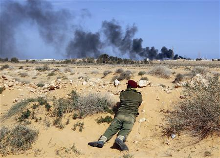 A rebel fighter lies prone on the ground during a battle along the road between Ras Lanuf and Bin Jiwad March 10, 2011. REUTERS/Goran Tomasevic