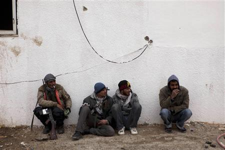 Libyan rebels sit at a checkpoint outside the city of Ajdabiyah, March 13, 2011. REUTERS/Finbarr O'Reilly