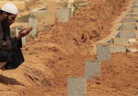 A mourner prays next to the grave of a rebel killed in Bin Jawad, during clashes with forces loyal to Libyan leader Muammar Gaddafi, in Benghazi's cemetery March 10, 2011. REUTERS/Suhaib Salem